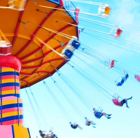 midway: People swing past with motion blur, shot to convey some of the excitement of the midway ride. Stock Photo