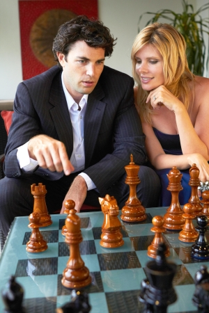 strategically: businessman strategically playing chess with supportive wife by his side.