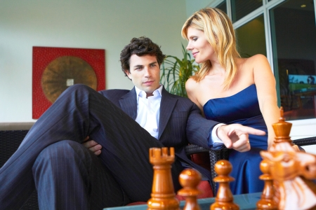 businessman strategically playing chess with supportive wife by his side. photo