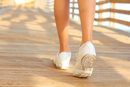 Close up of white sneakers walking the boardwalk. photo