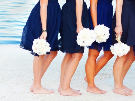 bridesmaids: A bride and her bridesmaids holding flowers at beach in Key West Florida