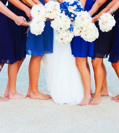 A bride and her bridesmaids holding flowers at beach in Key West Florida photo