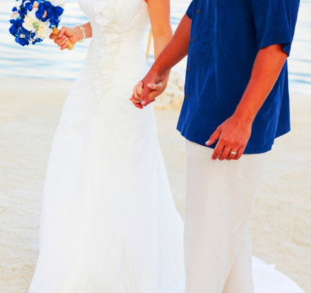 A bride and her groom holding hands walking photo