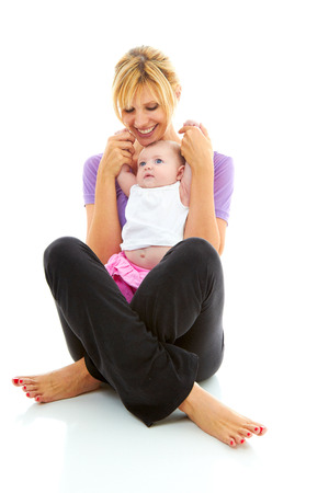 young beautiful caucasion mother holding her baby daughter doing baby yoga photo
