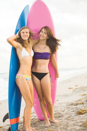 happy teenage girls at the beach with surfboards smiling photo