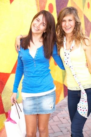 mini falda: Retrato del adolescente feliz con el brazo de pie alrededor de la bolsa de compras amiga. Tiro vertical.