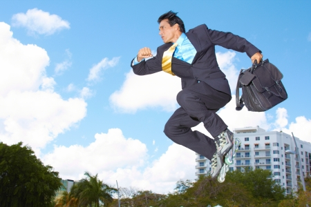 Businessman rollerblading with briefcase in urgency with cloudy sky in background. Horizontal shot. photo