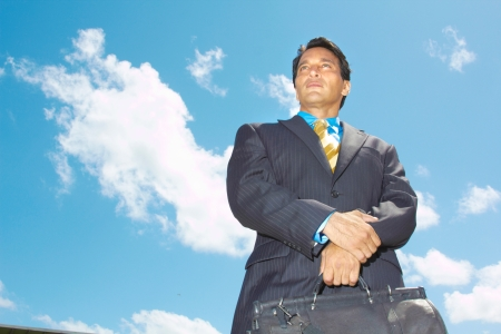 Low angle view of a confident businessman carrying briefcase against cloudy sky. Horizontal Shot. photo