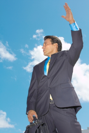 hailing: Low angle view of a young businessman hailing a taxi against cloudy sky. Vertical Shot.