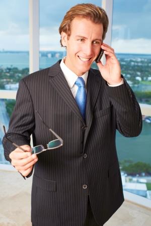 answering phone: Elegante var�n joven ejecutivo sonriente, mientras que la respuesta al llamado telef�nico. Tiro vertical.