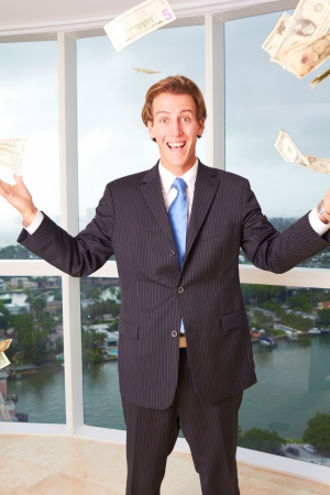 Portrait of excited young male business executive throwing money into air. Vertical shot. photo