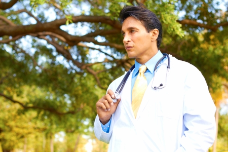 young male doctor: Handsome young male doctor with stethoscope looking away. Horizontal shot. Stock Photo