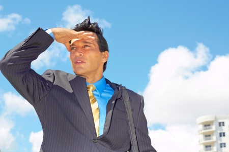 executive search: Confident young businessman shielding eyes for better vision against cloudy sky. Horizontal shot. Stock Photo