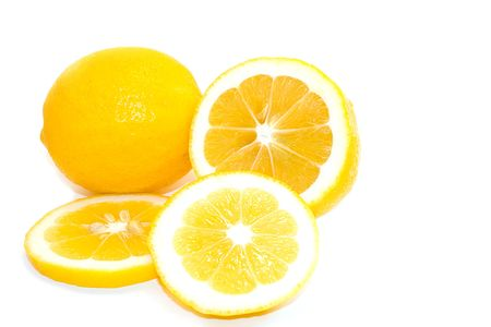 Whole and cut slices of bright yellow meyer lemons on white background.  Space for copy.