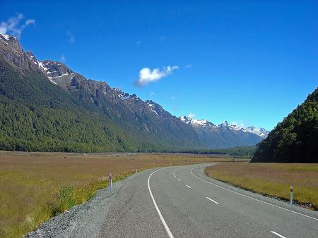 unsure: A New Zealand road disappearing into the distance backed by a snow capped South Island mountain range. Stock Photo