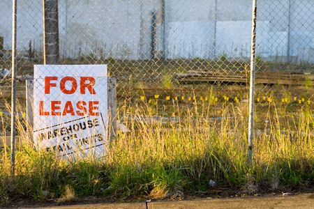 vacant land: A For Lease Sign on a vacant, part developed piece of land.  Space for copy.