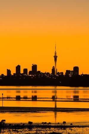 Auckland City in silhouette at sunrise viewed across the water, Auckland, New Zealand photo