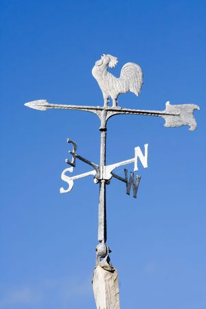 An old fashioned steel weather vane isolated against a bright blue sky