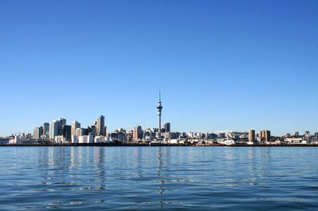 zealand: Auckland City and Sky Tower, New Zealand with bright blue clear skies viewed from across the harbour