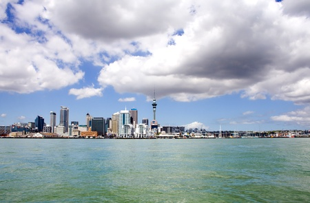 sky scraper: Auckland City and Sky Tower, New Zealand with cloudy skies viewed from across the harbour