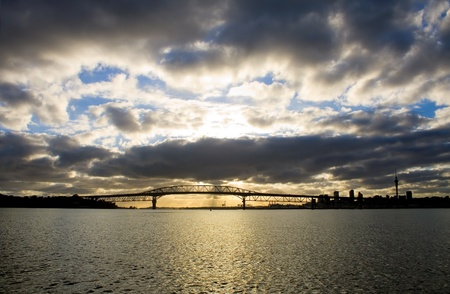A dramatic cloudy sunrise over the Auckland Harbour Bridge, Auckland City and Waitemata Harbour  photo