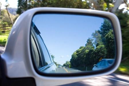 La vista mirando detrás a través de un espejo de vista lateral de coche Foto de archivo