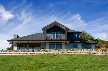 A modern house exterior positioned on a hill top with vibrant blue skies photo