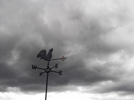Dark clouds behind a weather vane indicating bad weather and wind direction photo
