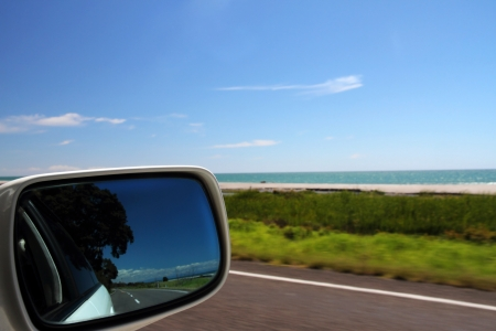 Unspoilt coastal views and the open road reflected in a car rear view mirror photo