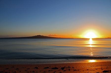 """wschód słońca: Åšwit nowego dnia jak sÅ'oÅ""""ce wznosi siÄ™ obok Rangitoto Island, Auckland, Nowa Zelandia"""