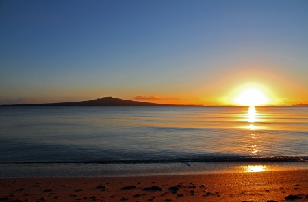 morning sunrise: The dawn of a new day as the sun rises beside Rangitoto Island, Auckland, New Zealand