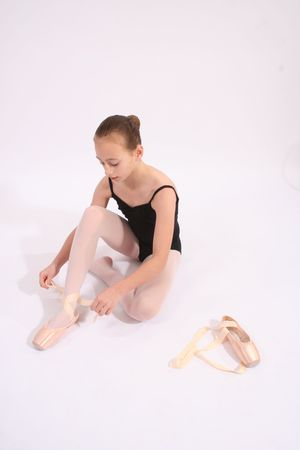 ballerina tights: Young girl dancer sitting tying ballet shoes