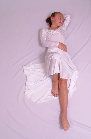 lyrical: Girl dancer in white lyrical dress sleeping on white sheet