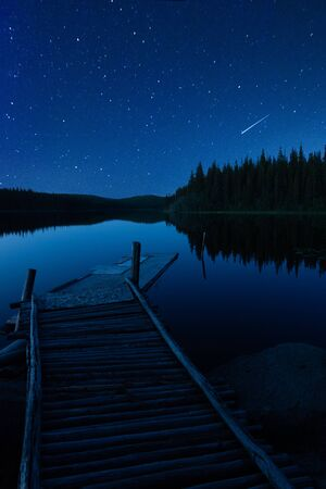 Vertical Landscape of A Pier and Starry Sky With A Comet