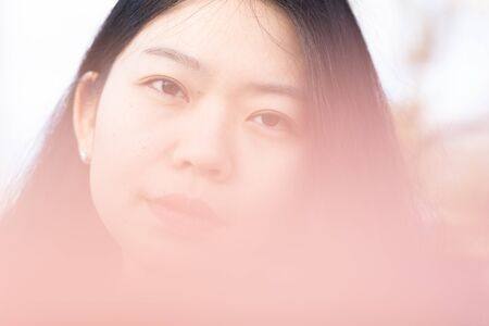 Soft Focus Background Of An Attractive Asian Woman Looking At The Camera Stock Photo