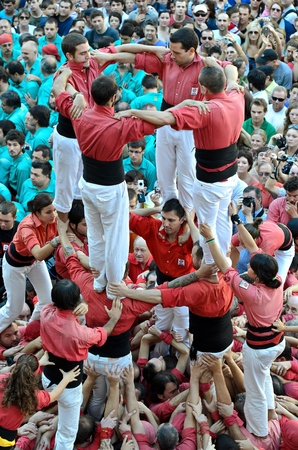 Members of Castellers de Barcelona build the traditional human tower at the Placa de Sant Jaume during the Mercé 2011 on September 25, 2011 in Barcelona, Spain. Editorial