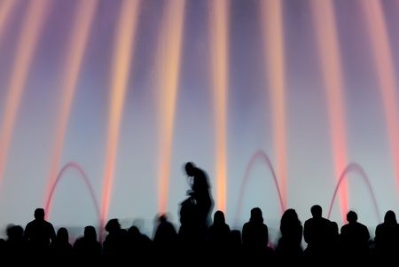 Magic fountains, Barcelona, Spain -  Silhouettes of people enjoying the colorful magic fountains in Barcelona, Spain, at night