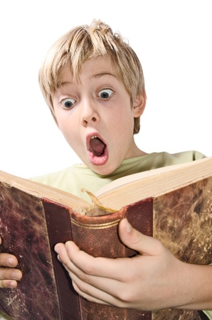 young boy reading scared in an old book Stock Photo
