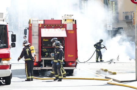 BARCELONA, SPAIN - MARCH 29: Fire workers slack one of the multiple fires caused by heavy riots during spanish general strike against labour reforms in the city center of Barcelona on March 29, 2912. Editorial