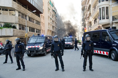 ugt: BARCELONA, SPAIN - MARCH 29: Police secures one of the multiple fires caused by heavy riots during spanish general strike against labour reforms in the city center of Barcelona on March 29, 2912. Editorial