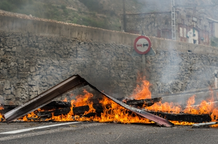 Striking miners barricade a national street and railway to protest against budget cuts in the coal industry and the shut down of the mines on June 19th 2012 in Ci�era, Spain Stock Photo - 14147385