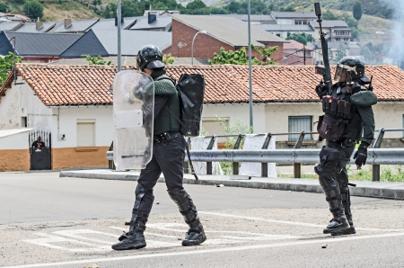 disperse: Anti riot police agents of the Guardia Civil disperse striking miners shooting rubber balls and smoke cans on June 19th 2012 in Ci�era, Spain Editorial