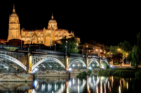 night view of the Cathedral of Salamanca, Spain behind the river Tormes