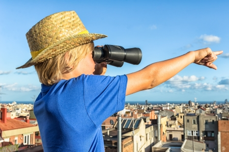 city watch - blonde boy overlooking city with binoculars photo