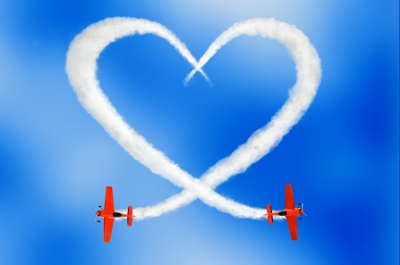 two air-planes drawing a cloudy love is in the air concept in the sky with smoke