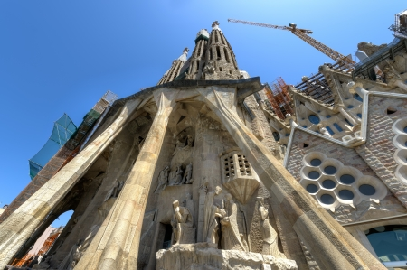 Passion facade of La Sagrada Familia - basilica designed by Antoni Gaudi, started in 1882 and still under construction at August 04, 2013 in Barcelona, Spain