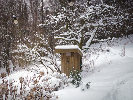 Old wooden toilet in a winter environment