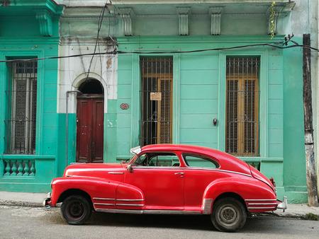 Red car in front of old building in Havana, Cuba
