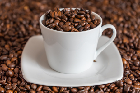Coffee beans in and around a cup