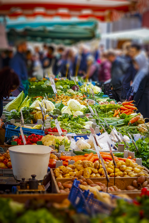 Colorful sales stand with vegetables at the market in Mainz with many people